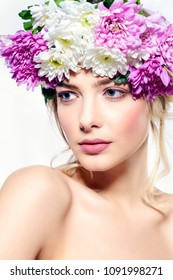 Close-up portrait of a sensual spring lady in a wreath of flowers. Beauty, cosmetics. Make-up. White background.