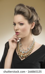 close-up portrait of sensual woman with aristocratic style posing with elegant hair-style and black dress, wearing big bright necklace