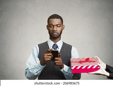 Closeup portrait serious businessman corporate executive holding looking at smart phone reading message, obsessed with it,  ignoring someones gift isolated grey black background. Human face expression