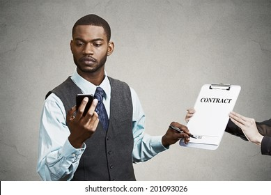 Closeup portrait serious businessman signing contract without looking at document, keeps reading news on smart phone holding mobile isolated grey background. Human face expression corporate executive