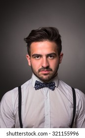 Close-up portrait of serious handsome man with bow tie on in photo studio. Bearded man in white shirt looking at the camera isolated on grey.