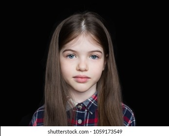 Closeup portrait of serious little girl isolated on black background