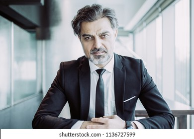Closeup portrait of serious middle-aged handsome business man looking at camera and sitting at table in office. Front view.