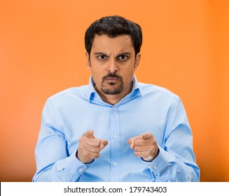 Closeup portrait of serious, staring, mad young man pointing at you with two index finger hands sign gesture, isolated on orange background. Negative human emotion facial expression feelings, symbols