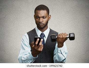 Closeup portrait serious worried business man reading bad news on smart phone holding mobile, lifting weight, dumbbell black grey background. Human face expression, emotion, corporate executive