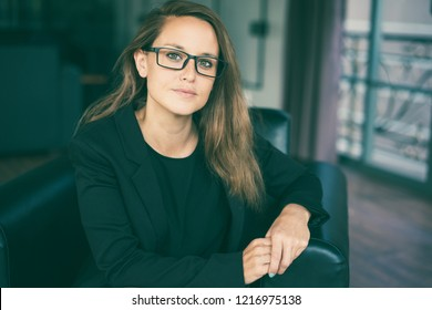Closeup portrait of serious young beautiful brown-haired woman looking at camera and sitting in armchair in hotel lobby. Beautiful business woman concept. Front view.