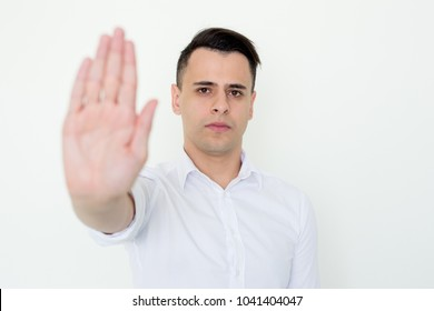 Closeup portrait of serious young handsome man looking at camera and showing blurred open palm or stop gesture. Stop concept. Isolated front view on white background.