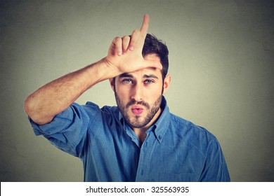 Closeup portrait of serious young man showing loser sign on forehead, looking at you with disgust at camera gesture isolated on gray background. Negative human emotions, facial expressions, feelings