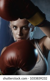 Close-up portrait of sexy blonde boxer woman with light eyes in red boxing gloves in front
