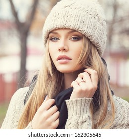 Closeup portrait of sexy blonde girl in knitted clothes. Looking at camera. Outdoors