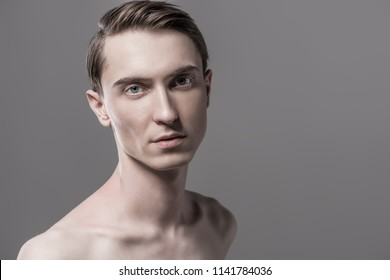 Close-up portrait of a sexy shirtless young man. Gray background. Men's beauty and health.