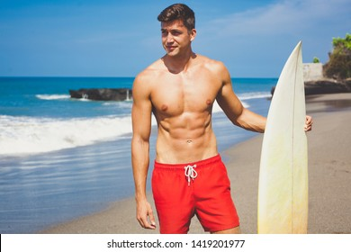 close-up portrait of Sexy very handsome tanned young man in red shorts and fit naked torso with a surfboard on the beach. surfer model