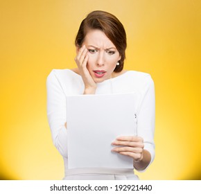 Closeup portrait shocked, funny looking young woman, disgusted at monthly statement, test, application, results isolated yellow background. Negative human emotion, facial expression, feeling. Bad news