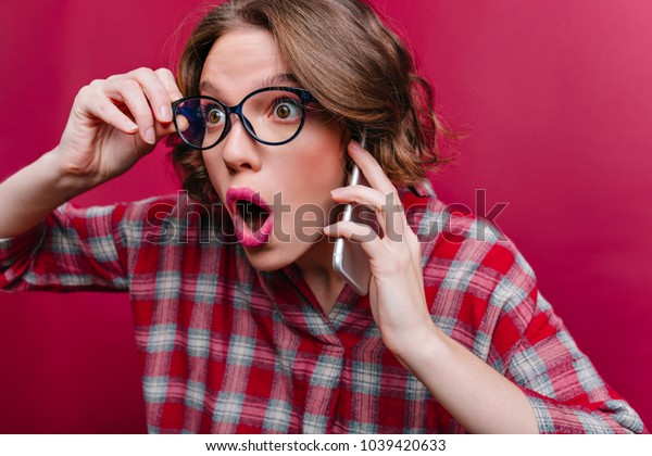 Close-up portrait of shocked girl in glasses talking on phone. Short-haired young woman in checkered shirt posing on claret background with surprised face expression.