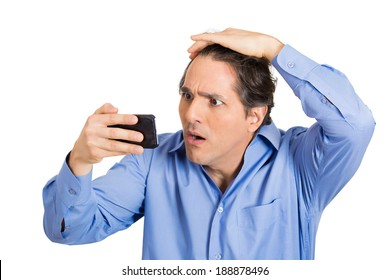 Closeup portrait, shocked man feeling head, surprised he is losing hair, receding hairline or seeing bad news on cellphone, isolated white background. Negative facial expressions, emotion feeling