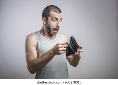 A close-up portrait of a shocked, surprised speechless man, holding an empty wallet