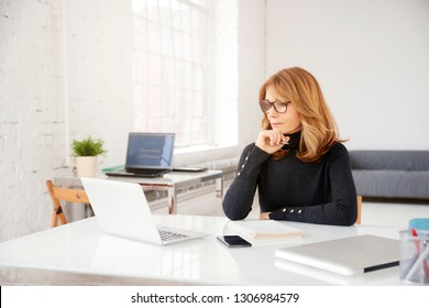 Close-up portrait shot of attractive businesswoman looking thoughtfully while sitting at office desk behind her laptop.