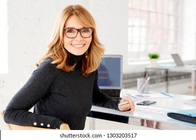 Close-up portrait shot of attractive mature businesswoman smiling to the camera while sitting at office desk and looking back.