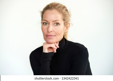 Close-up portrait shot of beautiful blond middle aged woman posing at isolated white background while looking at camera and smiling.