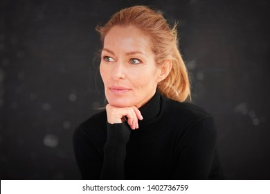 Close-up portrait shot of beautiful blond mature woman sitting at dark background while daydreaming.