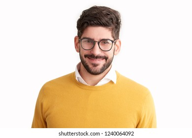 Close-up portrait shot of casual young businessman looking at camera and smiling while wearing glasses and sweater. Isolated on white background.