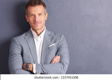 Close-up portrait shot of confident middle aged businessman with folded arms standing at grey wall and looking at camera.