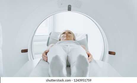 Close-up Portrait Shot of a Female Patient Lying on a CT or MRI Scan, Bed is Moving Inside the Machine While it Scans Her Body and Brain. In Medical Laboratory with High-Tech Equipment.