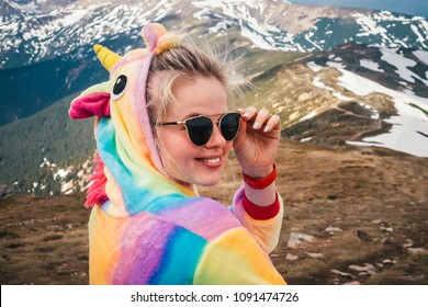 Close-up portrait shot in half-turn of a beautiful blonde female hiker wearing sunglasses and unicorn suit on the Carpathian mountain on a Spring day. Looking at camera. Wanderlust concept.