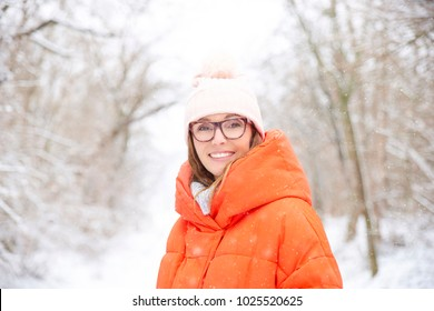 Close-up portrait shot a happy woman wearing hat and warm coat while standing outdoor and enjoy winter weather.