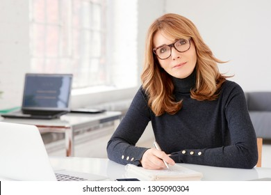 Close-up portrait shot of middle aged businesswoman wearing casual clothes while sitting at office desk and doing some paperwork.