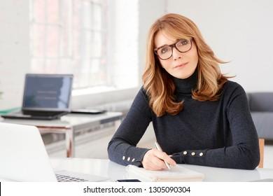 Nahaufnahme eines Porträts von Geschäftsfrauen mittleren Alters, die während ihrer Arbeit am Büroschreibtisch gelegene Gelegenheitskleidung trugen und Papierarbeit leisteten.