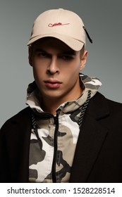 """Close-up portrait shot of a short-haired European man dressed in a dazzle hooded top, a black jacket and a beige baseball cap with an embroidered lettering """"Cablette"""" and decorated with a cable tie."""