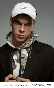 """Close-up portrait shot of a short-haired European man dressed in a dazzle hooded top, a black jacket and a white baseball cap with an embroidered lettering """"Cablette"""" and decorated with a cable tie."""