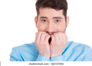 Closeup portrait shy, confused young guy, looking scared, shocked man biting nails, looking at you, craving something isolated white background. Human emotion facial expression, reaction