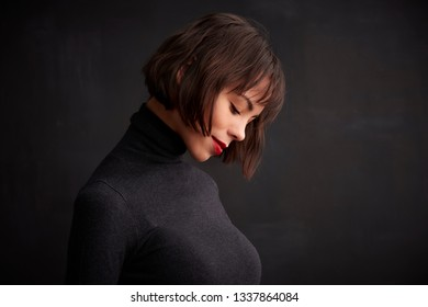 Close-up portrait shy smiling young woman wearing roll neck sweater while standing at dark background.