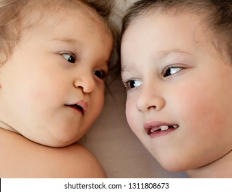 Close-up portrait of siblings looking at each other and lying on bed. Boy loves his disabled younger brother. -  image