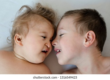 Close-up portrait of siblings looking at each other and lying on bed. Healthy boy loves his disabled little brother. -  image