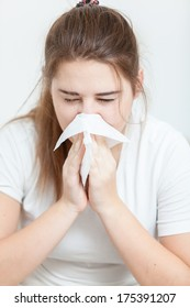 Closeup portrait of sick brunette girl sneezing in paper tissue