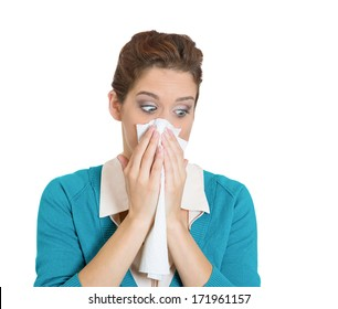 Closeup portrait of sick young woman student or worker with allergy or germs cold, blowing her nose with kleenex, looking miserable unwell very sick, isolated on white background. Flu season