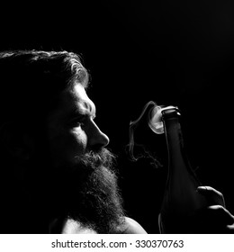 Closeup portrait side view of one senior serious man with long lush beard holding uncorked glass champagne wine bottle with smoke in studio on black background, square picture