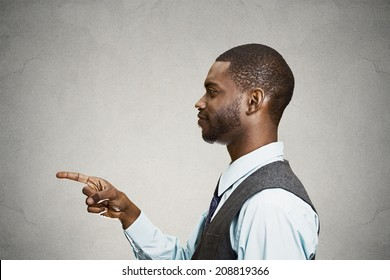 Closeup portrait side view profile young smiling handsome man pointing at you with index finger, isolated grey background. Human emotions, facial expressions, feelings, signs, symbols, body language