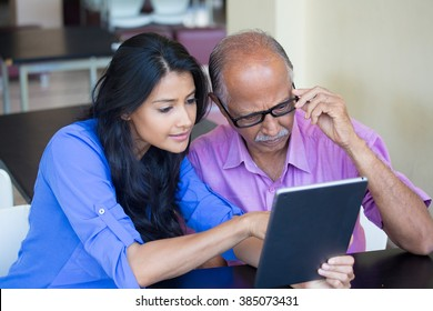 Closeup portrait, sitting young woman showing elderly with black glasses to use portable device,scrutinizing data with great concern, isolated indoors background