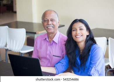 Closeup portrait, sitting young woman showing elderly man to use black laptop, smiling pose , isolated indoors background