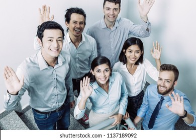 Closeup portrait of six joyful middle-aged business people gathering on office stairway, standing, looking at camera and waving with hands. High angle view.