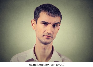 Closeup portrait of skeptical man looking suspicious, some disgust on his face mixed with disapproval isolated on gray background. Negative human emotions, facial expressions, feelings