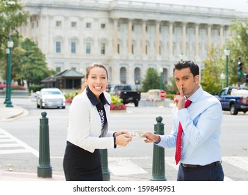 Closeup portrait of sleazy businessman or lobbyist offering money dollars bribe and saying shhh to happy corrupt politician in washington dc, isolated on Capitol building background