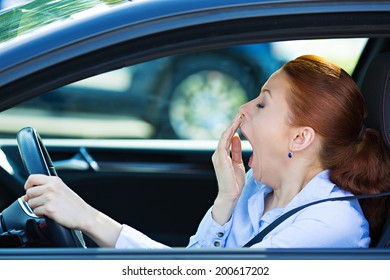 Closeup portrait sleepy, tired, fatigued, exhausted young attractive woman driving her car after long hour trip, isolated street traffic background. Transportation, sleep deprivation, accident concept