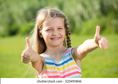 closeup portrait of small girl holding thumbs up on bright summer day
