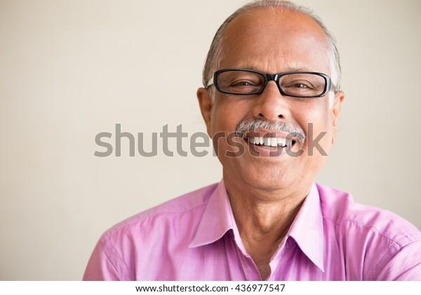 Nahaufnahme-Portrait, intelligenter älterer Mann auf rosafarbenem Hemd mit dunkler Augengläser, Spektren, lächelndes Sitzen, einzeln auf weißem Hintergrund