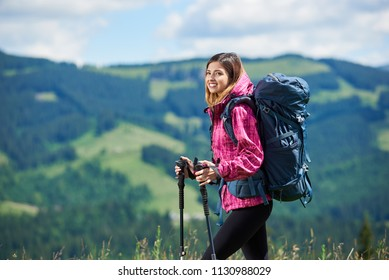 Close-up portrait of smiling active female backpacker with backpack and trekking poles, wearing sports wear, travelling, looking away, enjoying sunny day in the mountains. Copy space